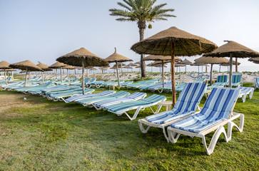 Sun umbrella on an empty beach and sea. Clear blue sky.