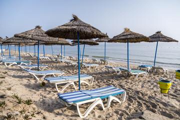 Sun umbrella on an empty beach and sea water horizon