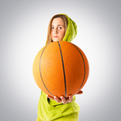 Blonde girl playing basketball over grey background