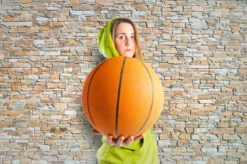 Blonde girl playing basketball over texture background