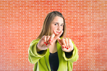 Girl doing NO gesture over bricks background