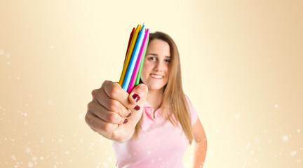 Blonde girl holding crayons over ocher background