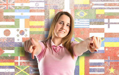 Young pretty woman pointing over flags background
