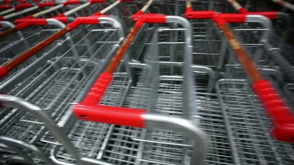 Many empty shopping carts in a row at parking of supermarket on