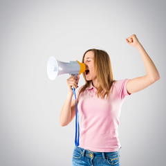 Blonde girl shouting with a megaphone over grey background