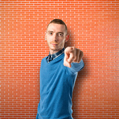 Young man pointing over isolated textured background