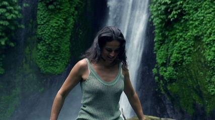 Happy woman running next to the waterfall, slow motion 240fps