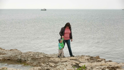 Mother And Baby Walking At the Seaside In Autumn