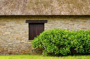 Natursteinfassade und Reetdach