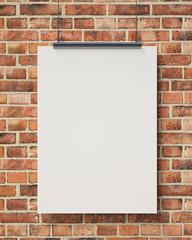 blank white hanging poster on brick wall