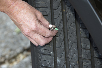 Woman using tyre depth gauge
