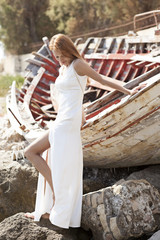 Beautiful young bride sitting on boat near the sea