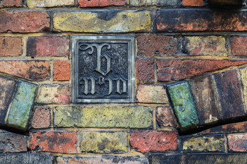 Art decor plate on old brickwork wall in Brugge, Belgium