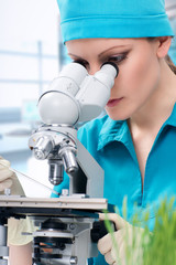 Woman biologist working with microscope