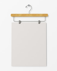 blank poster on clothes hanger hanging on the white wall