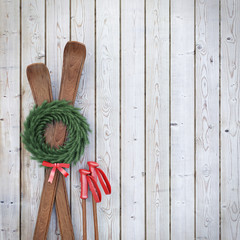 old wooden skis on wooden planks wall with garland