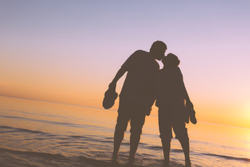 Happy senior couple silhouettes on the beach kissing