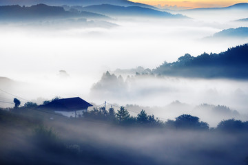 house on morning with misty mountains