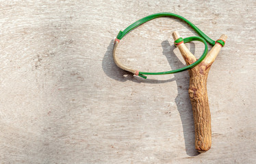 The old slingshot on old wood background.
