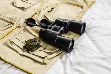 Compass and binoculars on safari suit