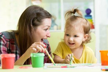 cute mother teach her daughter kid to paint