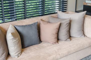 pillows on brown sofa