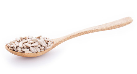 Sunflower seeds in wooden spoon on white background
