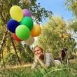 Frau mit Luftballons im Gras