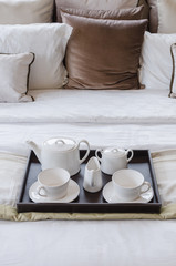 tray of tea set on bed
