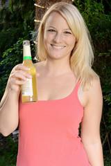 Frau trinkt Fassbrause auf Party im Garten
