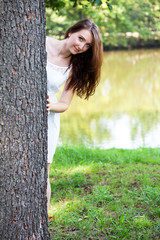 Woman hiding behind the tree