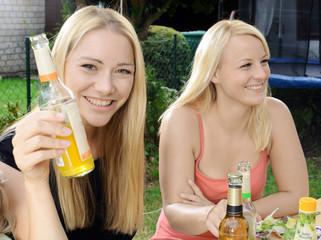 Freundinnen feiern im Garten und trinken Fassbrause