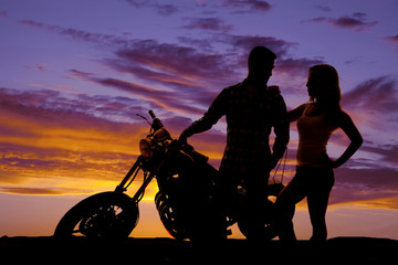 silhouette couple stand by motorcycle