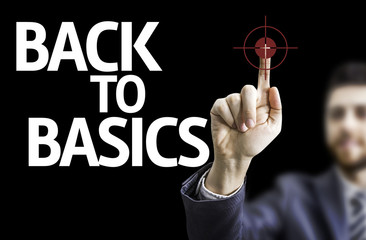 Business man pointing the text: Back to Basic