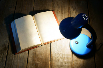The open book and the fixture. On wooden background.