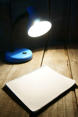 Notebook and the fixture. On wooden background.