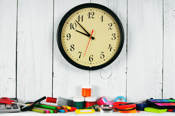 Watches and school tools. On white, wooden background.