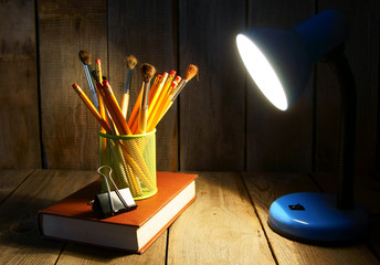 Pencils and books. On wooden background.