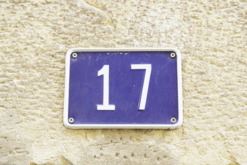 Number seventeen on the wall of a house
