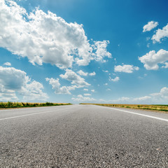 asphalt road to horizon and clouds over it