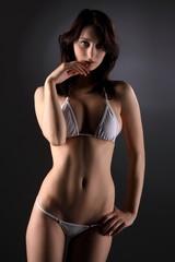 Sexy busty brunette girl posing in a white bikini