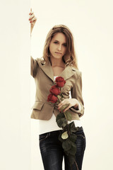 Young fashion woman with a roses at the wall