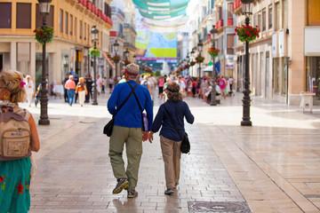 A senior couple walking at Larios street, Málaga.