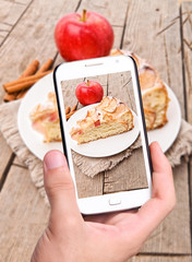Hands taking photo apple cake with smartphone
