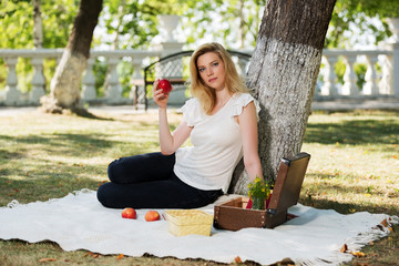 Young fashion woman with apple in a city park