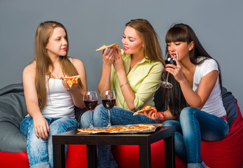 Three girls with wine and pizza