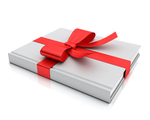 blank white book lying as gift with red ribbon