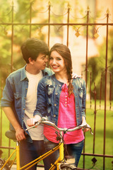 Young couple with bicycle outside