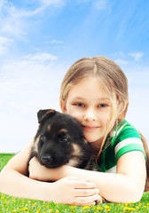 little cute girl on a green lawn hugging a puppy