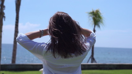 Woman touching hair and stand against seaside, slow motion240fps